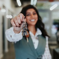 Picutre of an ONE Street real estate agent holding up ONE Street car keychain